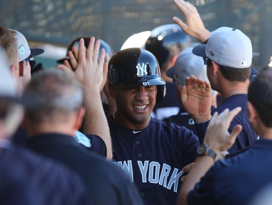 Gleyber Torres is greeted in the dugout after he scored