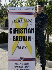 Navy Aviation Ordnanceman Christian Brown, 21, poses for a photo with his BRAVE Project banner Wednesday morning.