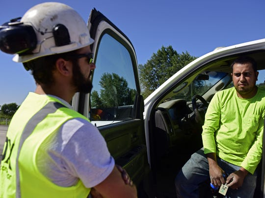 Martin Baez (right), a crew leader for BX Construction, talks with project supervisor Nic Kahler (left) during Baez's lunch break. Baez is one of the handful of Spanish-speakers working for the company that has a commercial driver's license. Unlike most states, South Dakota only offers its driving exams in English. The restriction has become a workforce problem in a fast-growing construction industry that depends on immigrant labor.