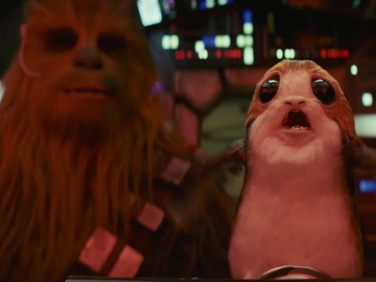 """Among the new characters introduced in """"Star Wars: The Last Jedi"""" are the birds known as """"porgs,"""" one of which is shown here hitching a ride with Chewbacca on the Millennium Falcon."""