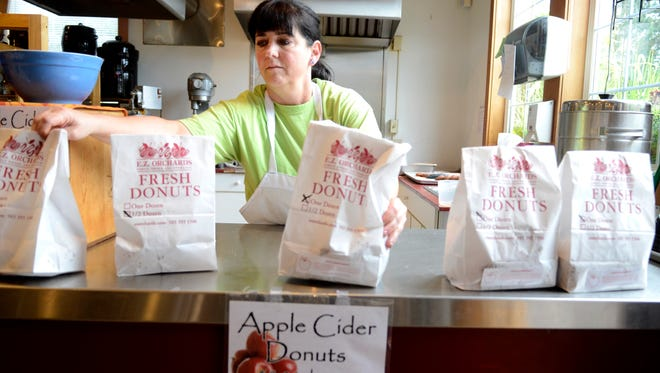 Dorothea Kearns bags apple cider doughnuts at E.Z. Orchards outside Salem on Tuesday, Oct. 14, 2014. The doughnuts are back this month.