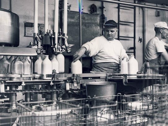 Delbert Burke lifts the ready-for-market milk off a conveyor belt after a machine seals the cap in a 1961 Courier-Journal photo showing the end of processing, after milk is put into sterilized glass bottles.