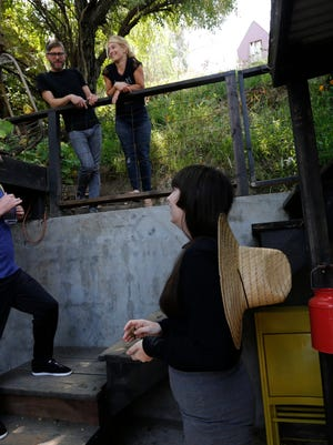 File photo shows ceramist and Airbnb host Jonathan Entler, top left, and his daughter Ruby, top right, talking to guests, James Green, bottom left, and Camille Smithwick from Manchester, U.K., at their Echo Park home in Los Angeles.