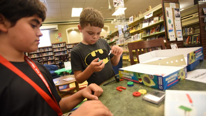 Cole Cosimano (age 8, R) plays with magnetics as Tal Ledeniov (age 12, foreground), a volunteer, looks on  during a drop-in program that allows children to experiment with various technology and create things, photographed at Glen Rock Public Library on July 18th, 2017.