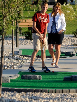 File - Steven Manis and his mother Diane Manis, both of Manitowoc, take part in a trial run of the new miniature golf course at the Manitowoc Family Aquatic Center in Citizen Park in 2014.