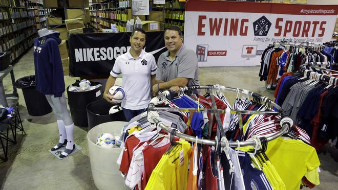 Chris Goodrich, left, and Les Korsos, pose with sale racks stocked with soccer uniforms and gear at a warehouse of their company, Ewing Sports, that sells mostly soccer uniforms to school and other teams, in Ewing. Key employees at the company, Goodrich and Korsos bought Ewing Sports from their retiring bosses in July.