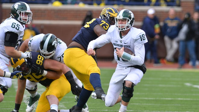 MSU's Connor Cook slides down at the end of a run against Michigan in Ann Arbor on Oct. 17.