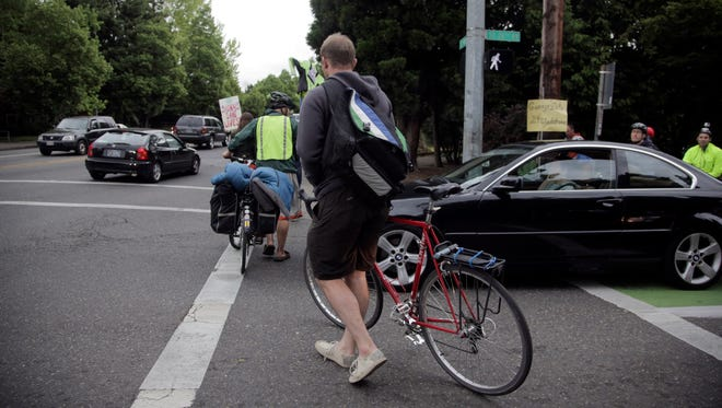 Cyclists, neighbors, friends and family of Alistair Corkett rallied at the intersection of SE 26th Avenue and Powell Monday, May 11, 2015, during rush hour to bring attention to traffic issues there. Corkett's leg was amputated after a car hit him while he was riding his bike through the intersection Sunday.