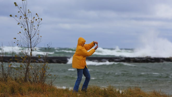 A woman is blown back by wind as she tries to capture photos of waves inside the Muskegon breakwater on Thursday.