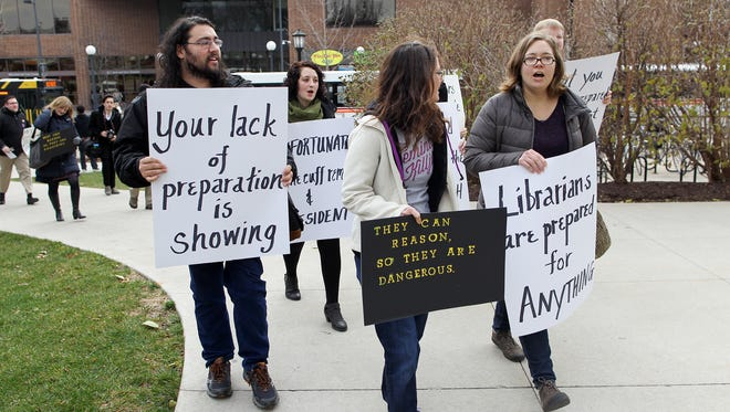A group of protesters march through the Pentacrest to University of Iowa President Bruce Harreld's office on Thursday, Dec. 17, 2015.