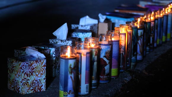 Candles and tissue boxes sit near the front of a vigil