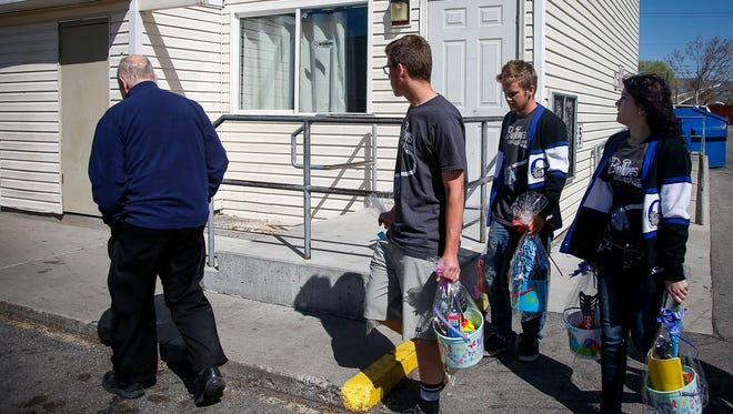 """Students from Gunnison Valley High School, organized by Don Ward (left), a retired high school history teacher, hand out Easter baskets to refugees in South Salt Lake, Utah. The service was part of the LDS Church's """"I Was a Stranger"""" initiative supporting refugees."""