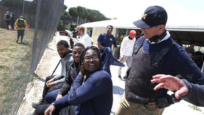 Michigan football coach Jim Harbaugh, right, talks with Rashan Gary during team-building time playing paintball at Speedball Roma Club on their third day in Rome on Tuesday, April 25, 2017.