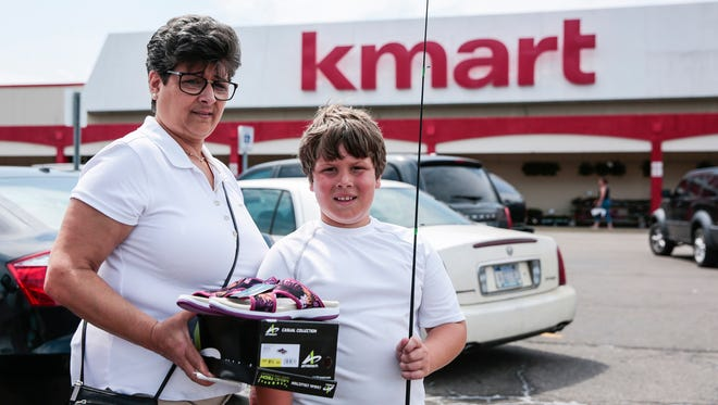 Anne Moschouris, left, and her grandson Nikolas Moschouris,10, both of Harper Woods, pose for a photo with a pair of sandals and a fishing rod they just purchased from Kmart outside of the store, Wednesday, June 14, 2017 in St. Clair Shores.