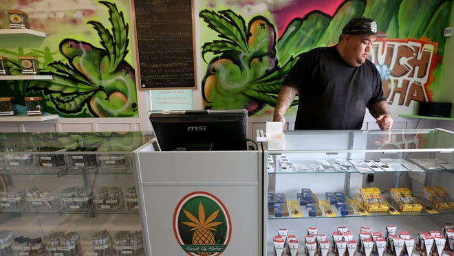 Shane Ramos-Harrington, the owner of Touch of Aloha Cannabis Dispensary, helps a customer in his shop outside Depoe Bay along the Oregon Coast on Wednesday, May 17, 2017.