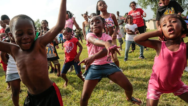 Foreground left to right: Jakyi Wilson, Kya Washington and Kylnn Hobbs, all of Detroit, dance with a crowd as a dj plays music in July 2017 during the United Way for Southeastern Michigan Meet Up and Eat Up Block Party at the Joseph Walker Williams Recreation Center in Detroit.
