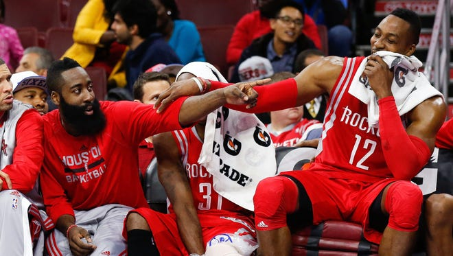 Houston Rockets guard James Harden (left) and center Dwight Howard (12) joke around on the bench at the end of a recent game.