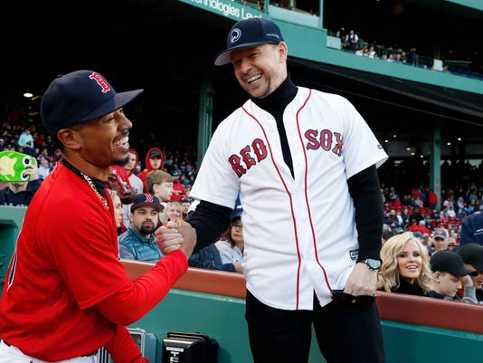 Donnie Wahlberg, right, shakes hands with Boston Red Sox's Mookie Betts, left, as Jenny McCarthy, seated right, looks on before a baseball game against the Tampa Bay Rays in Boston, Friday, April 14, 2017. (AP Photo/Michael Dwyer)