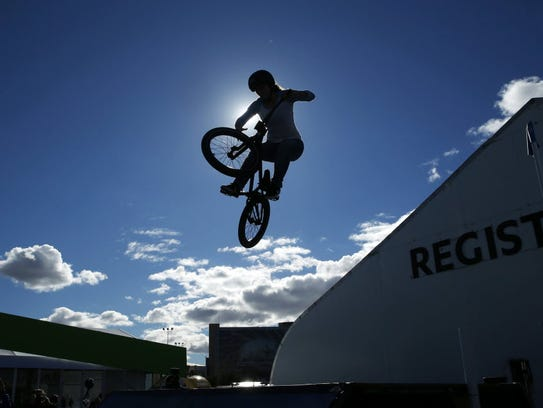 Perris Benegas performs a stunt on her bike at an Intel