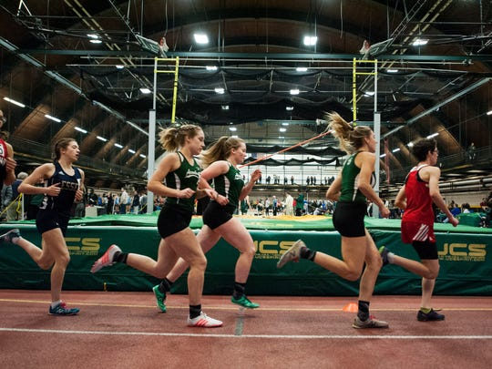 Runners compete in the girls 1,500m race during the high school indoor track and field championships at Gutterson Field House on Saturday February 10, 2018 in Burlington.