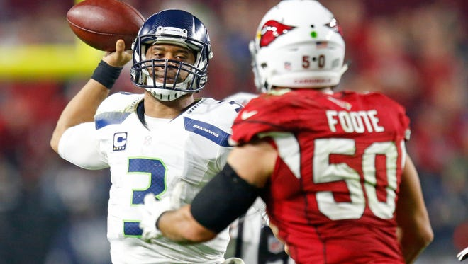 Seattle Seahawks quarterback Russell Wilson (3) throws under pressure from Arizona Cardinals middle linebacker Larry Foote (50)  in the 4th quarter quarter of their NFL game on Dec. 21,  2014 in Glendale.