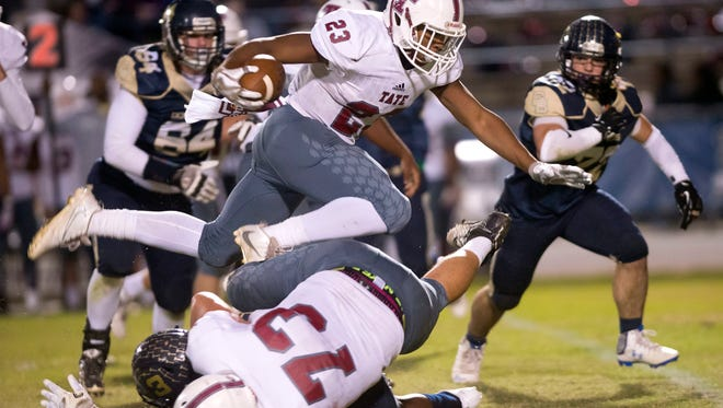 Tate High School's Shamari Jones, (No. 23) leaps over his blocker, Tyler Dorsett, (No. 73) to pickup a few extra yards against the Gulf Breeze High School defense. Jones, Dorsett and two other players from Tate signed letters of intent as part of National Signing Day.