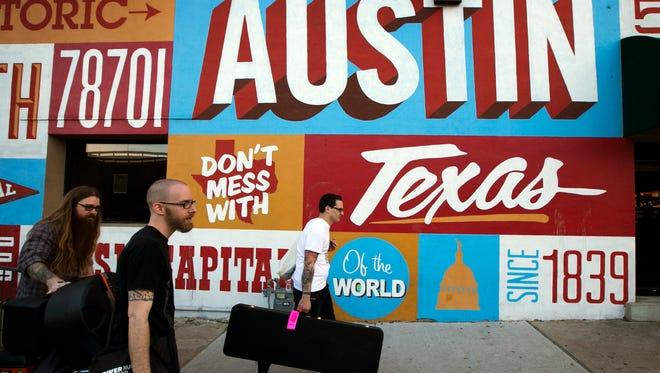 Zak Jordan, middle, and Mikey Centrella, right of the Washington DC punk band The Mostly Dead, and their friend Seth Beall, left, walk to a gig at the Dizzy Rooster on Sixth Stret at SXSW on Wednesday March 18, 2015.   (AP Photo/Austin American-Statesman, Jay Janner)