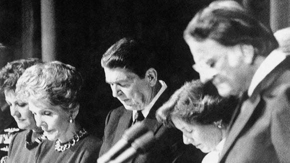 President Reagan bows his head and prays during the
