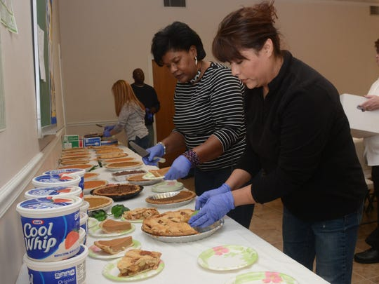 """Volunteers Sharon Brinson (left) and Beatriz Basco prepare to help serve Thanksgiving dinner for the Salvation Army in Alexandria. """"It's a real blessing to be healthy and able to help others,"""" Brinson said."""