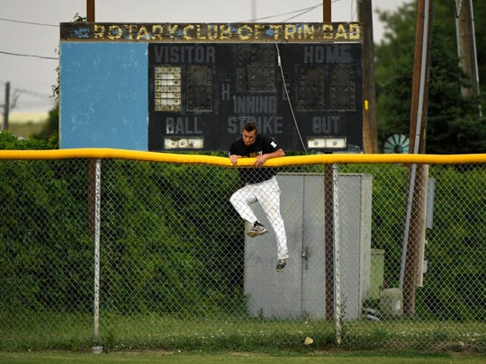 Trinidad Triggers pitcher #23 Jake Heissler climbs the outfield fence after turning on the field lights during their game against the White Sands Pupfish at Trinidad's Central Park. The team does everything during and before the games to upkeep the field, watering, smoothing and lining. June 22, 2017 in Trinidad, CO.