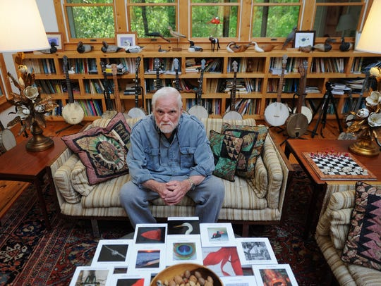 Bates Littlehales poses in his living room with a collection