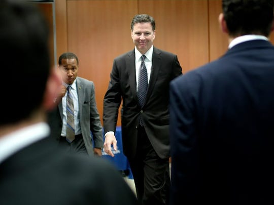 FBI Director James Comey, center, leaves the room after speaking at a press conference on Tuesday, April 5, 2016, at the Federal Reserve Bank in Detroit, MI.