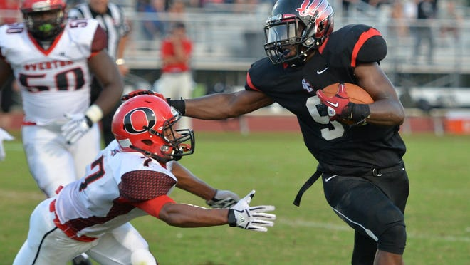 Stewarts Creek's Jordan Rouse stiff-arms an Overton defender. The Red Hawks defeated the Bobcats 16-8.