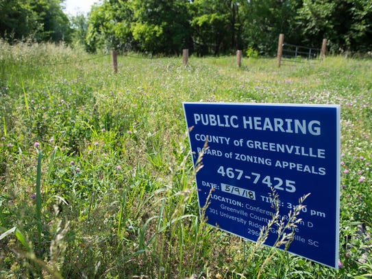 A sign promoting a pubic hearing sits in an empty lot