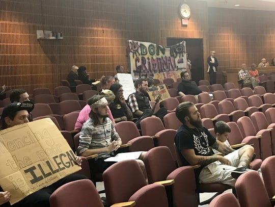 Opponents of the panhandling ordinance hold signs on