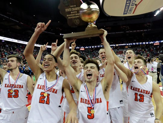 Members of the Kaukauna boys basketball team celebrate
