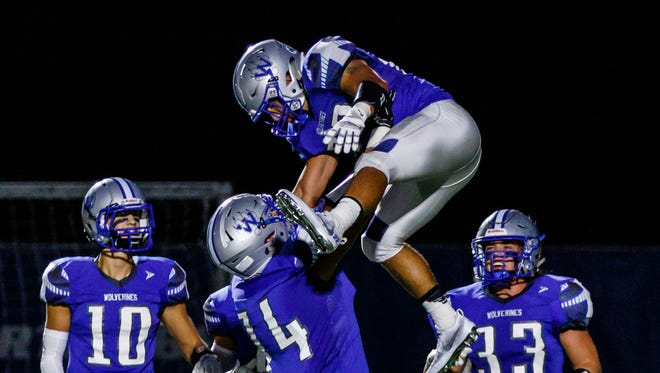 Waukesha West lineman Bryce Texeira (74) hoists teammate Peter MacCudden (22) into the air for a touchdown celebration during the game at home against Germantown on Thursday, Sept. 7, 2017.