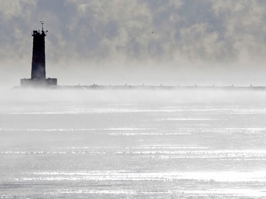 The Sheboygan lighthouse looks lonely among the steam rising from Lake Michigan due to the cold morning temperatures.