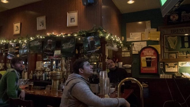 From left: Mike Colley, Jason Kaczmarczyk, and owner of O'Leary's, Engus O'Leary watch a soccer game between the Arsenal and Monaco while Dooly's Encore plays a O'Leary's on Beacon Street on St. Patrick's Day, March 17, 2015.