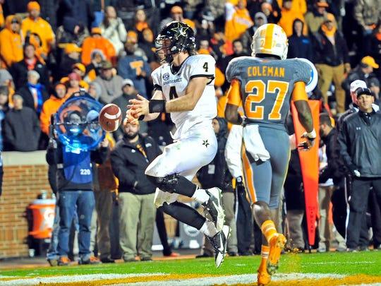 Vanderbilt quarterback Patton Robinette (4) scores the game-winning touchdown past Tennessee defensive back Justin Coleman during the fourth quarter at Neyland Stadium in Knoxville, Tenn., Saturday, Nov. 23, 2013. Vanderbilt won 14-10.