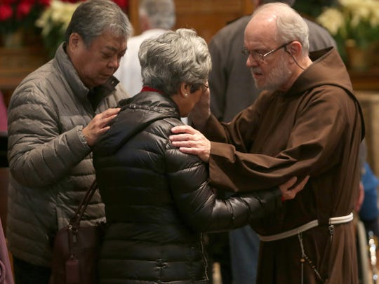 Brother Richard Merling blesses and prays with people