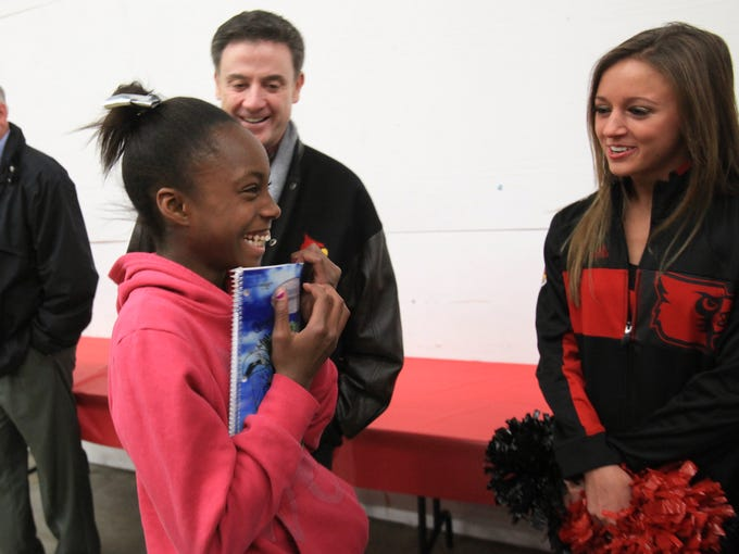 Ce-Onna Beason, 10, left, was thrilled as she approached the U of L Ladybirds during a holiday shopping event with U of L basketball players, Ladybirds and community children at the Meijer on Hurstbourne Pkwy.  Coach Rick Pitino was in the background. Dec. 12, 2013