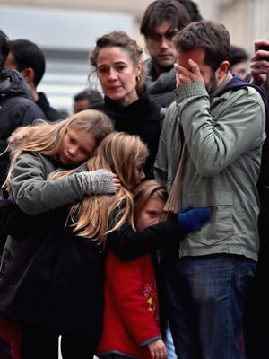 Mourners gather in front of the Le Petit Cambodge and Le Carillon restaurants on Nov. 14, 2015, in Paris. Both places were targeted by terrorists.