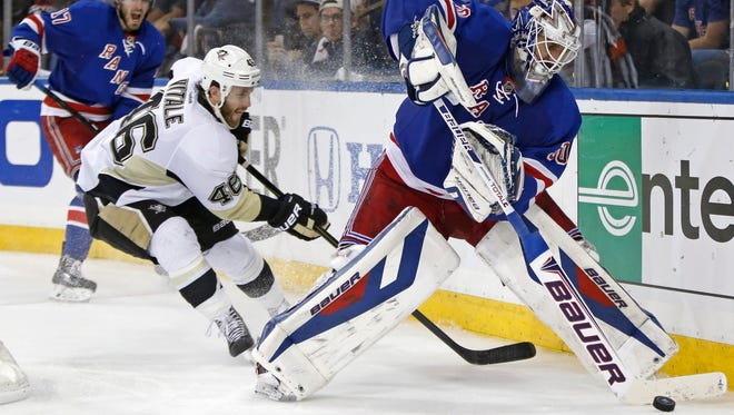 Rangers goalie Henrik Lundqvist clears the puck behind the net as Pittsburgh Penguins center Joe Vitale (46) pursues during Game 6 Sunday night.
