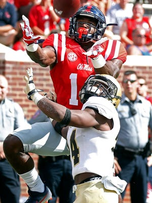 Mississippi wide receiver D.K. Metcalf (14) reaches over Wofford cornerback Devin Watson (24) to catch a 10-yard touchdown pass in Oxford Saturday.