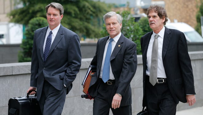 """Former Virginia Gov. Bob McDonnell, center, arrives Aug. 18, 2014, at federal court in Richmond, Va., with his lawyers John Brownlee and and Henry """"Hank"""" Asbill for the start of the McDonnell defense."""