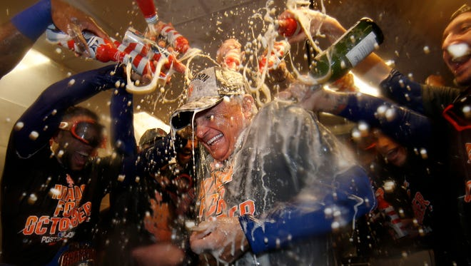 Mets manager Terry Colllins is doused with champagne and beer by his players.
