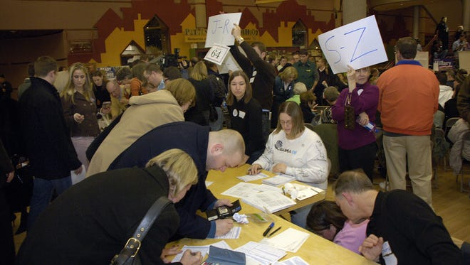 People sign in before the start of a precinct caucus held at the State Historical Building in Des Moines on Jan. 3, 2008.