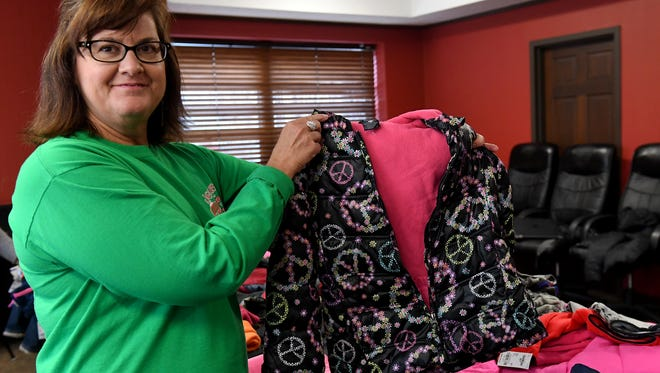 Sherry Cole, Madison County director of services at the Carl Perkins Center, holds up one of the coats donated in their coat drive.