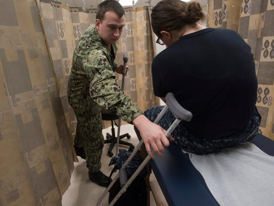Navy Corpsman Petty Officer 3rd Class Travis Huffman, left, treats a sailor Wednesday for a lower leg injury during clinic hours at the Naval Air Technical Training Center on board Pensacola Naval Air Station.